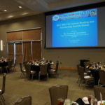 Large event room with tables and slideshow